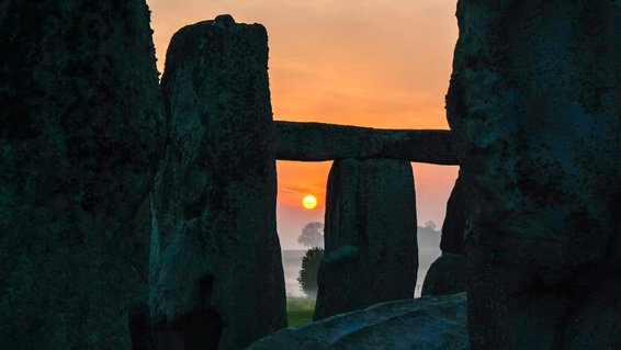Rising sun viewed through the stones at Stonehenge in Wiltshire, UK