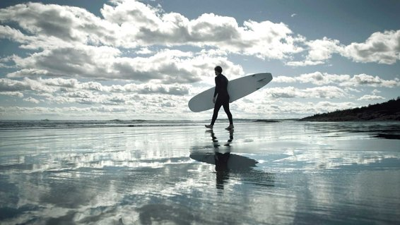 Surfer walks towards water, Higgins Beach, Maine.