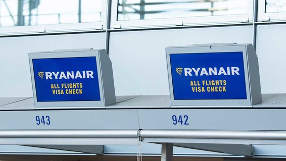 Irish airline Ryanair logos are displayed on monitors at the check-in counter