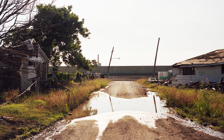 A repaired levee, at the end of a street flanked by destroyed homes, 2005.