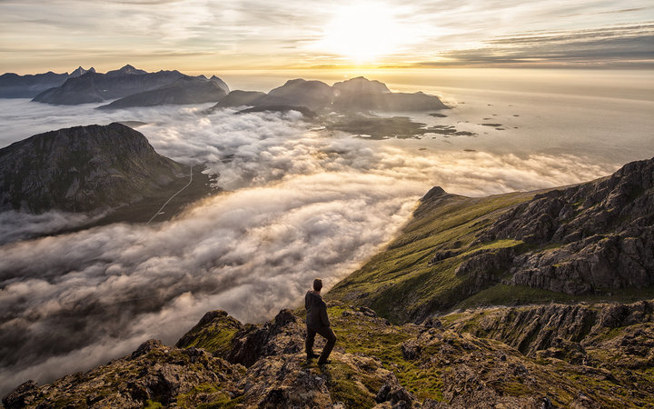 Man above the clouds on mountain Lofoten Norway