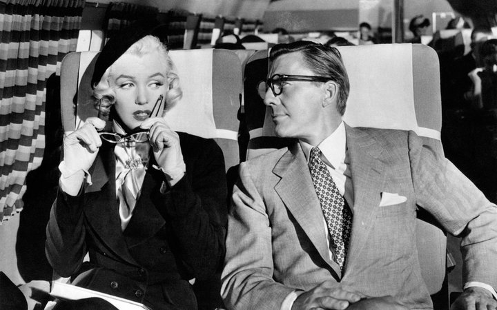American actors Marilyn Monroe (Norma Jeane Mortenson) and David Wayne (Wayne James McMeekan) sitting in an airplane in the film How to Marry a Millionaire. USA, 1953 (Photo by Mondadori Portfolio via Getty Images)