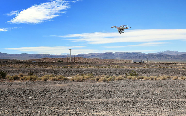 Young man remote control drone flying in the blue sky of Los Angeles California,October 10,2014