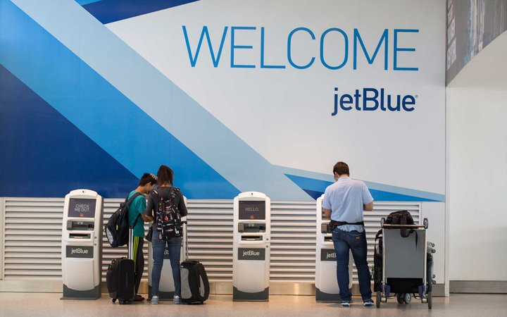 Travelers check in at JetBlue Airways Corp.'s Terminal 5 at John F. Kennedy International Airport (JFK) airport in New York, U.S., on Friday, Aug. 7, 2015. The largest airline at JFK by passengers, JetBlue will be building a 505-room, $250 million TWA Fli