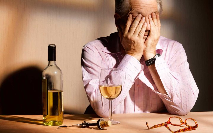Exhausted man having a glass of wine.