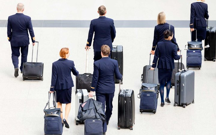 Group of cabin crew walking at the Hong Kong International Airport, carrying their luggage