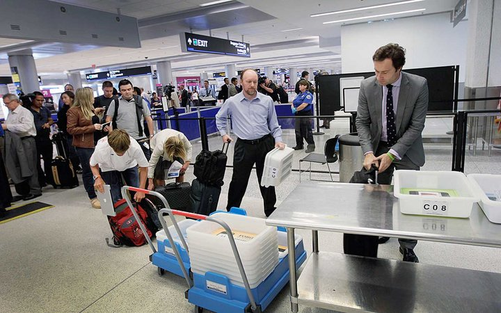 MIAMI, FL - OCTOBER 04:  Passengers wait to clear security next to the newly opened TSA PreCheck lane which the Transportation Security Administration launched to cut down the time prescreened passengers need to stand in the traditional security line at M