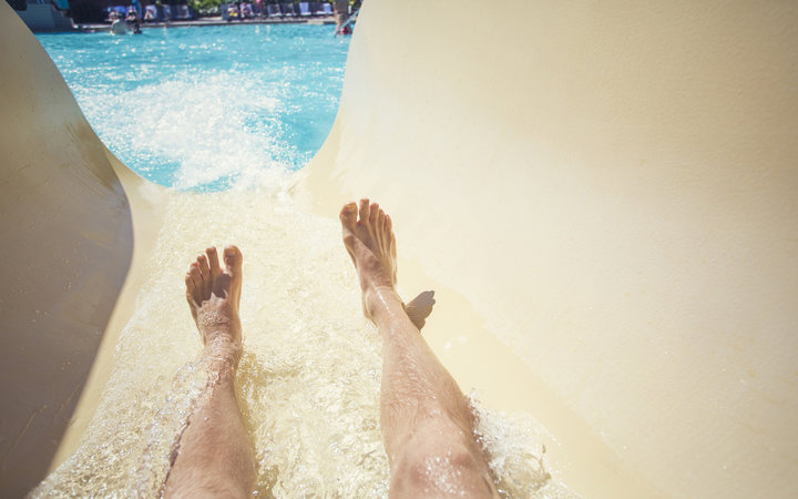 Point of view photo of a men going down a waterslide at an outdoor waterpark during a warm summer day. Lots of copy space. Focus on the feet and water slide