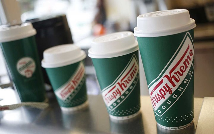 Coffee cups sit in a row inside a Krispy Kreme Doughnuts Inc. store in Louisville, Kentucky, U.S., on Monday, May 9, 2016. Krispy Kreme Doughnuts Inc. agreed to be acquired by a JAB Holding Co. subsidiary in a $1.35 billion deal. Photographer: Luke Sharre
