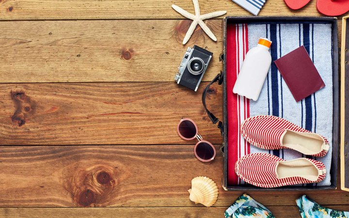 Directly above shot of open suitcase with summer vacation accessories. Flat lay of travel and beach equipment. They are placed on right side of hardwood floor. The copy space on floor can be used for advertisement purpose.