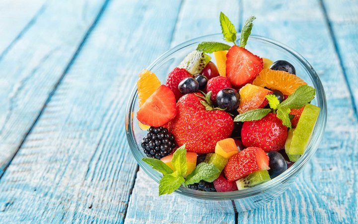 Fresh fruit salad with various kind of berry and citrus fruit served in glass bowl, placed on wooden table
