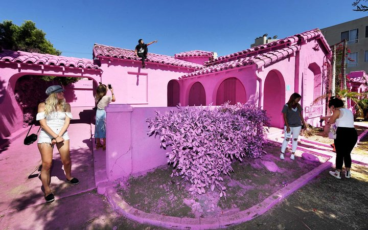 People pose for photos at the  Pink Houses  which have become an pop-up photo opportunity after a local developer hired artist Matty Mo to paint the three houses pink, before there eventual demolition in Los Angeles, California
