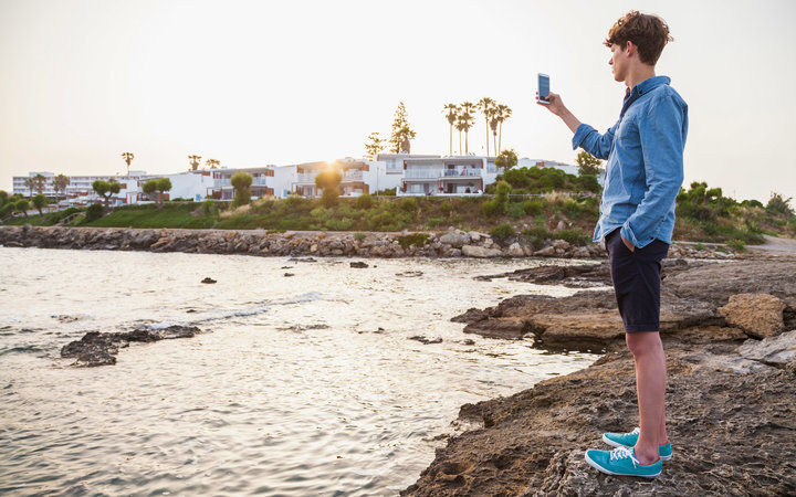 Greece, Rhodes, young man photographing with smartphone at seafront