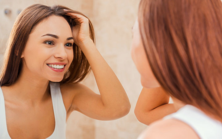 Beautiful young woman touching her hair with hand and smiling while standing in front of the mirror