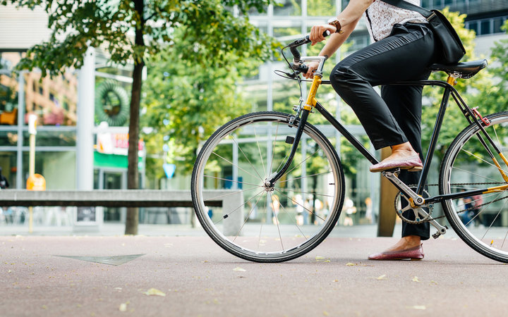 Close up shot of businesswoman's legs riding a bicycle