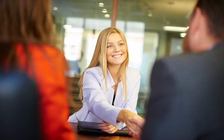 a young graduate sits across the table from her interview panel  full of confidence and positivity energy . She is holding her cv and smiling at the interview panel before her and shakes hands with the new boss.She is wearing blue trousers with an orange