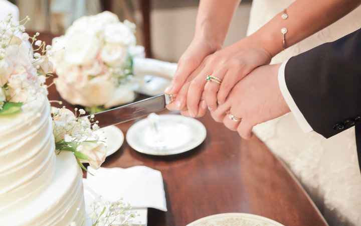 Couple's hands cutting their wedding cake.