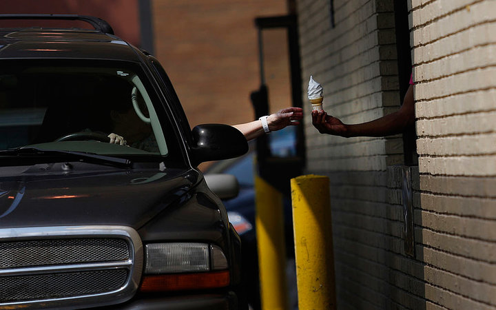 A driver receives a soft serve ice cream cone from an employee working the drive-thru at a McDonald's Corp. restaurant in Louisville, Kentucky, U.S., on Monday, July 21, 2014. McDonald's Corp., the largest restaurant chain by sales, posted second-quarter