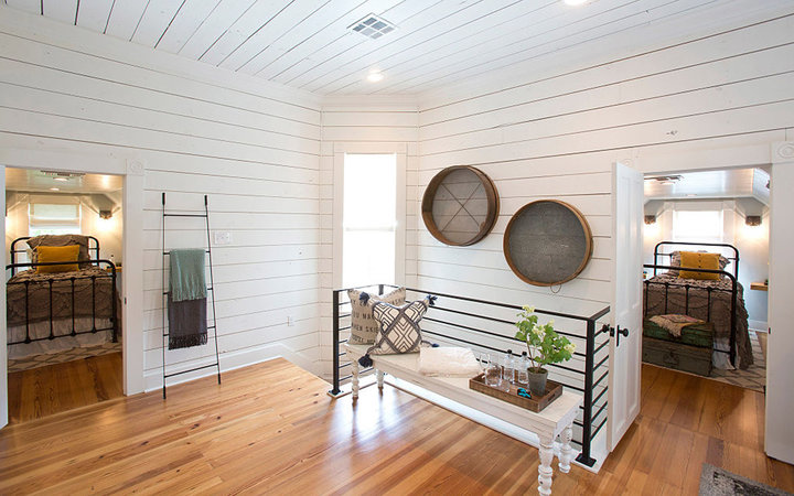 At the top of the stairs is a spacious landing that got new wood flooring, white shiplap, a bench seat and a modern railing. (Ross Hailey/Fort Worth Star-Telegram/TNS via Getty Images)
