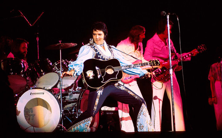 UNITED STATES - JULY 20:  Photo of James BURTON and Elvis PRESLEY; with James Burton on guitar (behind Elvis) performing live onstage,  (Photo by Steve Morley/Redferns)