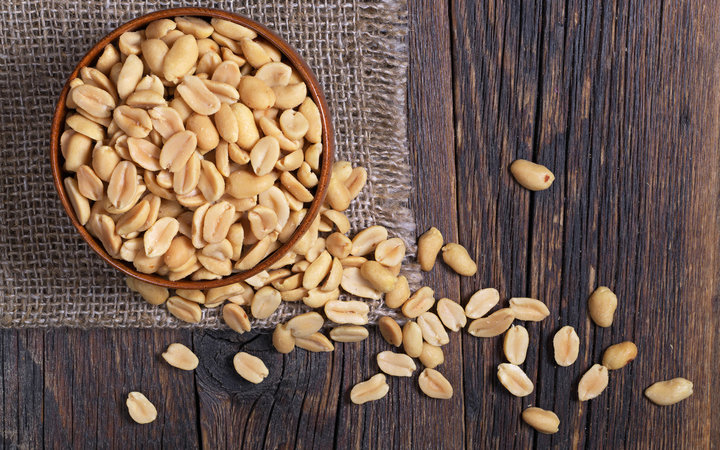 Halves of roasted peanuts in bowl and near on dark wooden background, top view