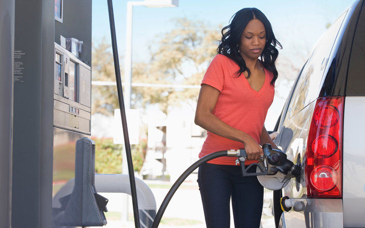 African American woman pumping gas at gas station