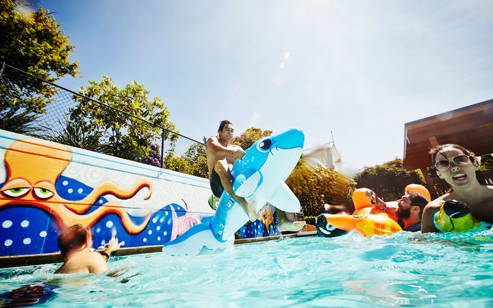 Man jumping into outdoor pool on inflatable toy during party with friends swimming in the background