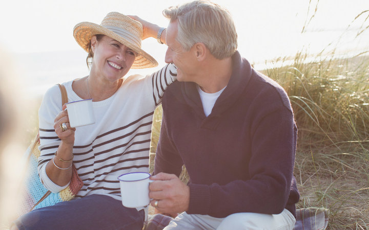 Mature couple drinking coffee on the beach