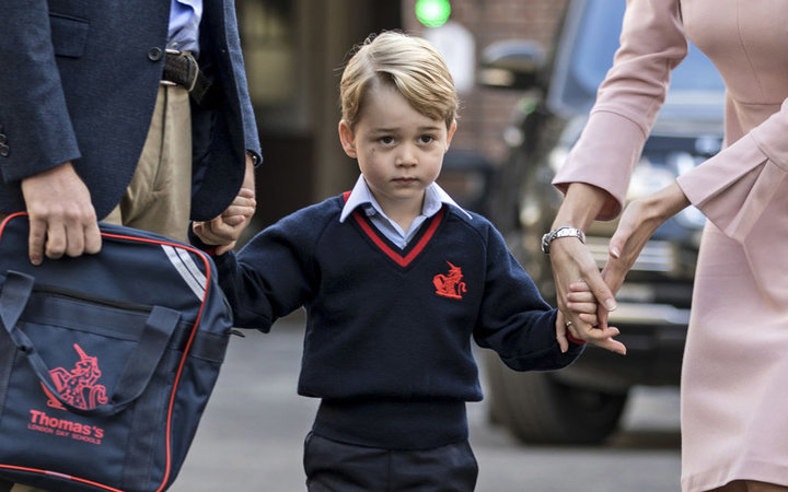 Britain's Prince George (C) accompanied by Britain's Prince William (L), Duke of Cambridge arrives for his first day of school at Thomas's school where he is met by Helen Haslem (R) head of the lower school in southwest London on September 7, 2017. / AFP