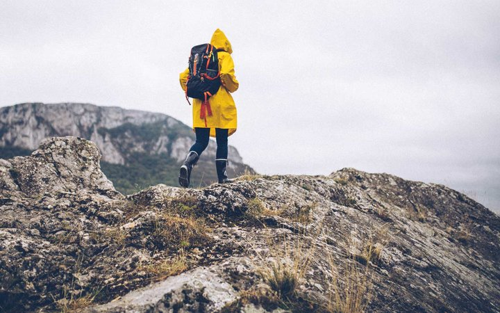 Woman in yellow raincoat hiking in wet weather
