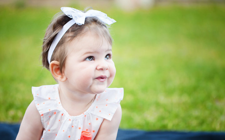 Cute baby girl sitting on the grass looking away