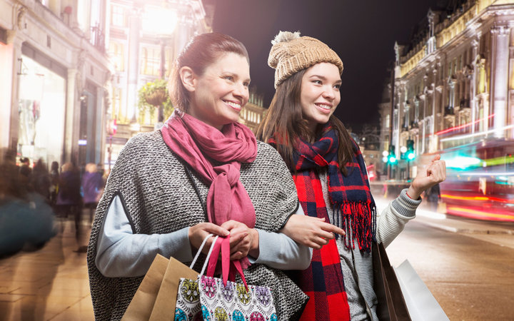 Mother and daughter shopping in busy street.