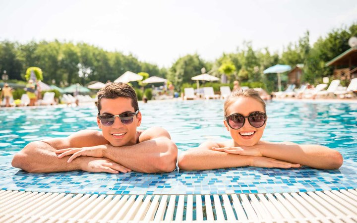 Happy couple in a pool, wearing sunglasses