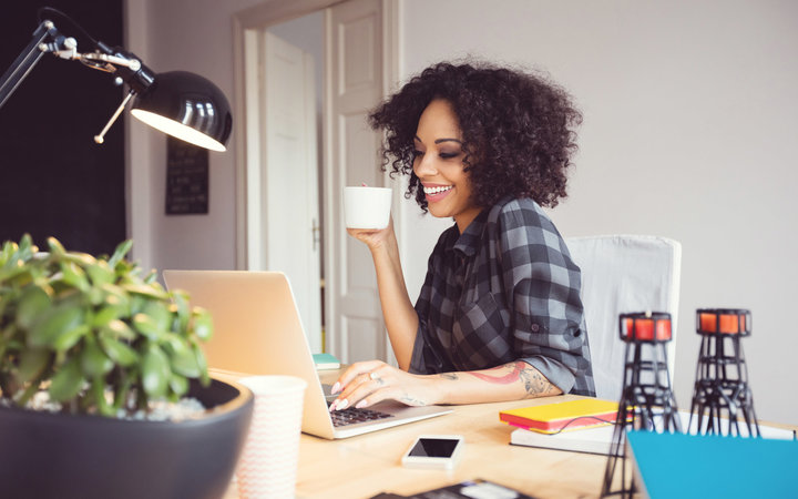 Afro young woman in the home office, using laptop