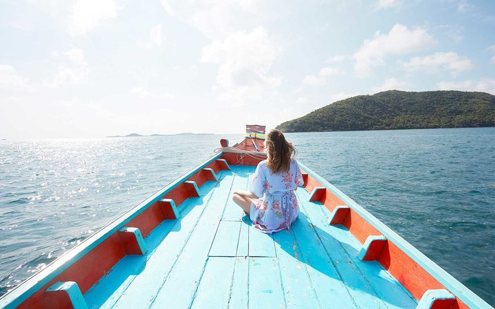 Young woman sitting on blue boat