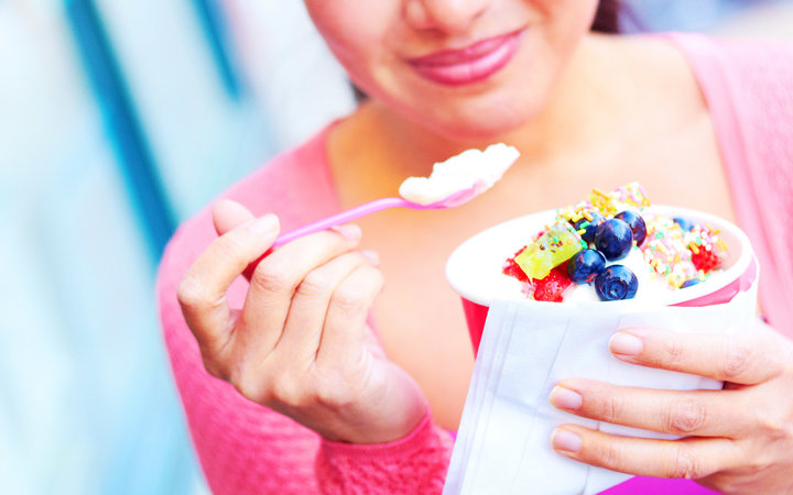 Young woman eating frozen yogurt topped with assorted sweets