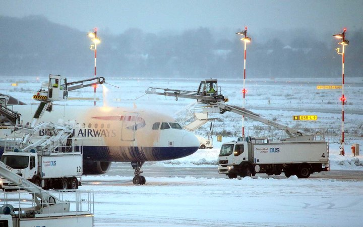 An airplane of British Airways is being de-iced as it stands on the tarmac.