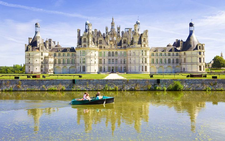 Chambord Chateau reflected in the canal as a family sails by in a boat