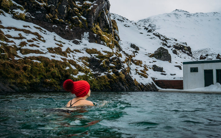 Woman in stocking cap swimming below snowy mountains, Iceland