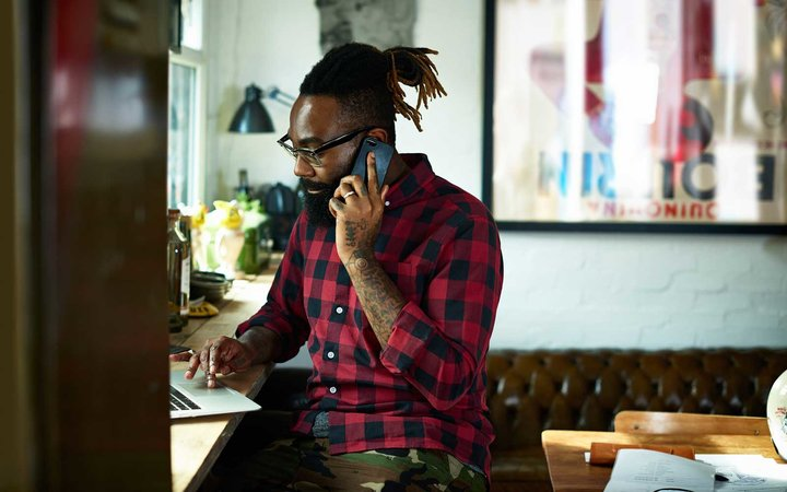 Man using laptop and mobile phone in studio.