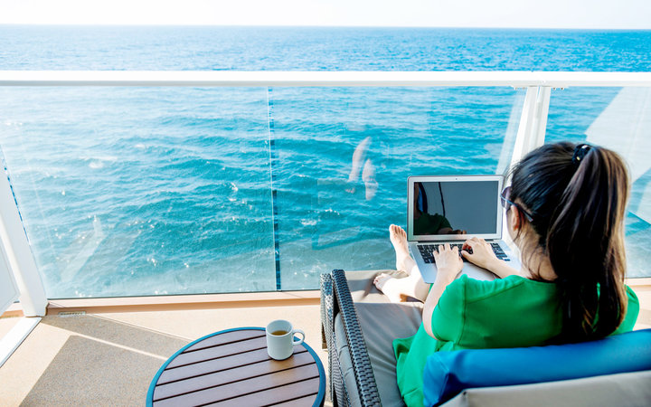 Woman working with a laptop on cruise ship.