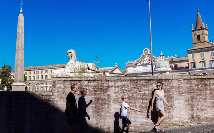 Tourists family walking down a street rounding Piazza del Popolo
