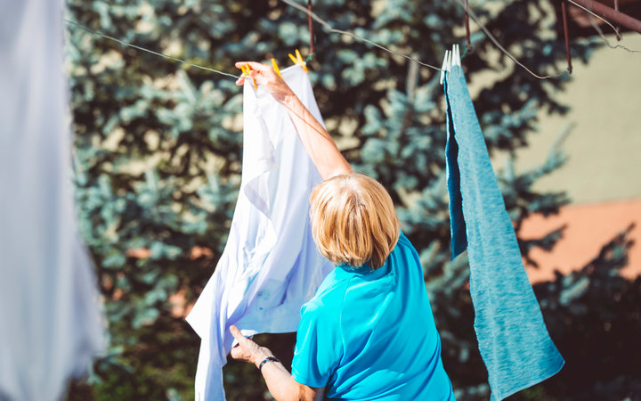Mature woman hanging clothes to dry on clothes-line