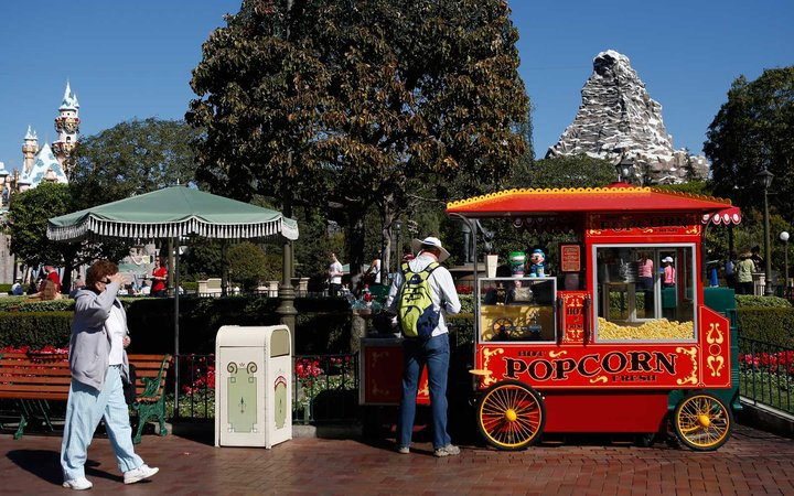 A Cast Member serves popcorn to guests near the Magic Castle and Matterhorn at Disneyland
