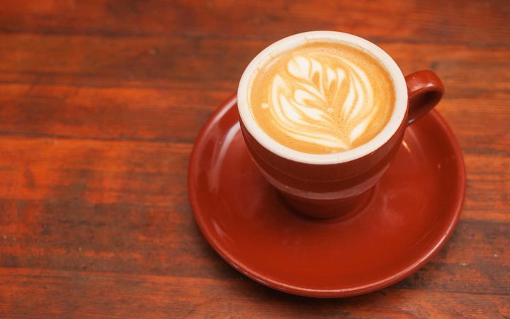 Cappuccino in a red cup on a wooden table