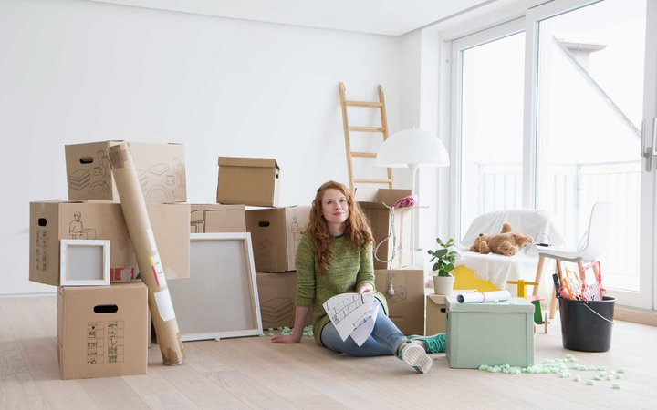 Young woman in new flat with cardboard boxes holding ground plan