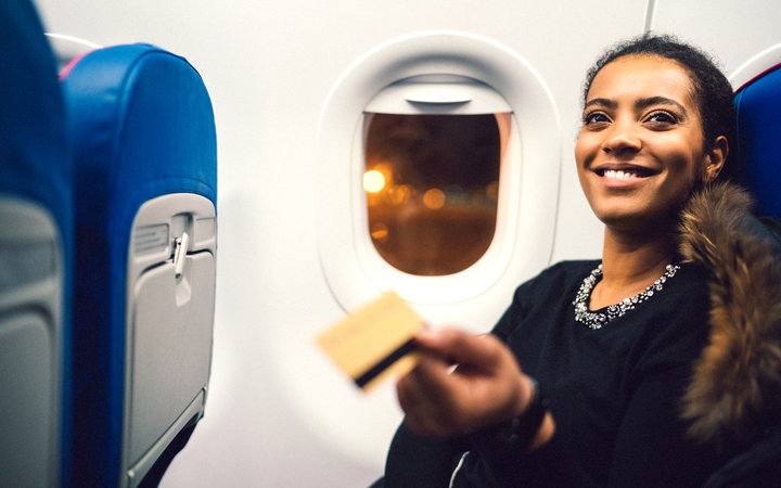 Young woman in airplane shopping with credit card