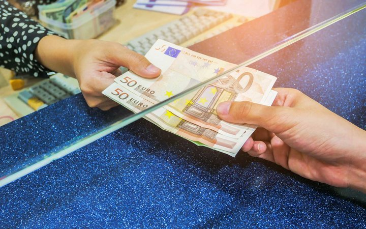 Female hand with money in cash department window. Currency exchange concept.