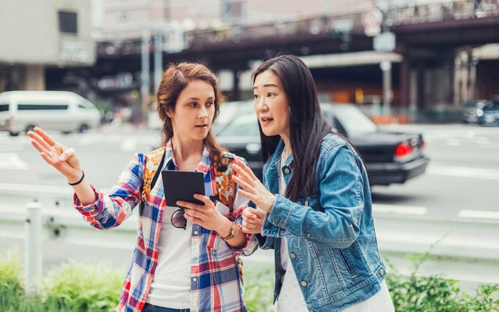 Young woman in Tokyo asking for direction a local woman
