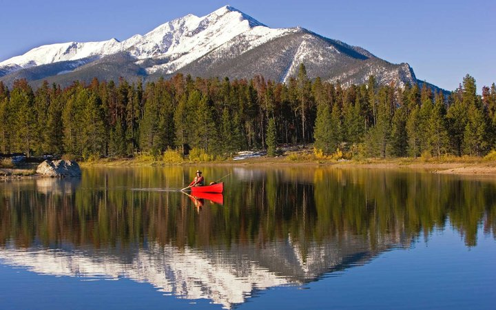 Photo of a man fly fishing and canoeing on Lake Dillon in Summit County, Colorado.